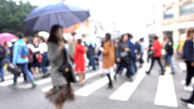 雨の日に横断歩道を歩いている人々 - 中国 広州市点の映像素材/bロール