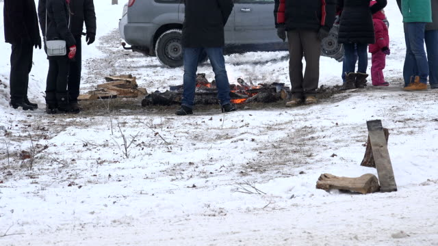 People warm near fire place in cold winter day. video