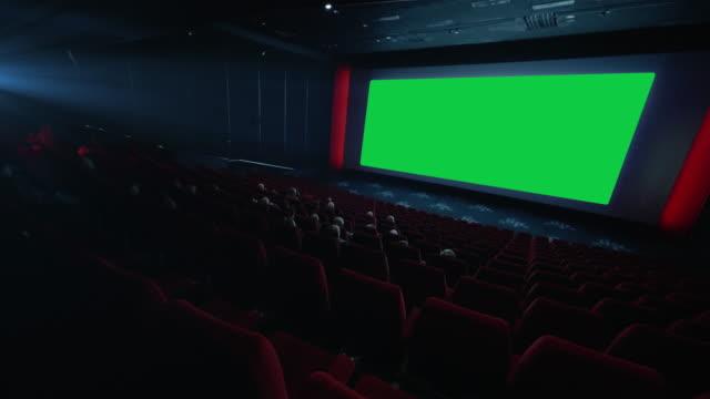4K - People watching movie in cinema theater. green screen. chroma key