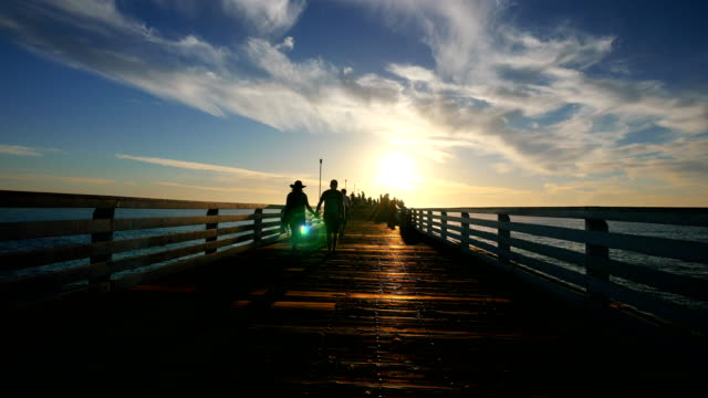 people watching the sunset on the pier in 4k - molo video stock e b–roll