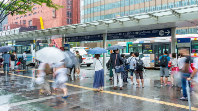People wating at bus stop near Hakata station Fukuoka, Japan - 13 July 2019 - Japanese people wait for their bus at a bus stop near Hakata station in Fukuoka, Japan on July 13, 2019 bus stop stock videos & royalty-free footage