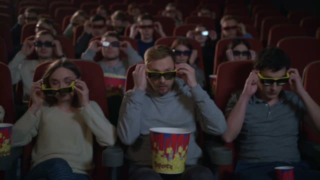 people wearing 3d movie glasses in cinema. movie entertainment - movies стоковые видео и кадры b-roll