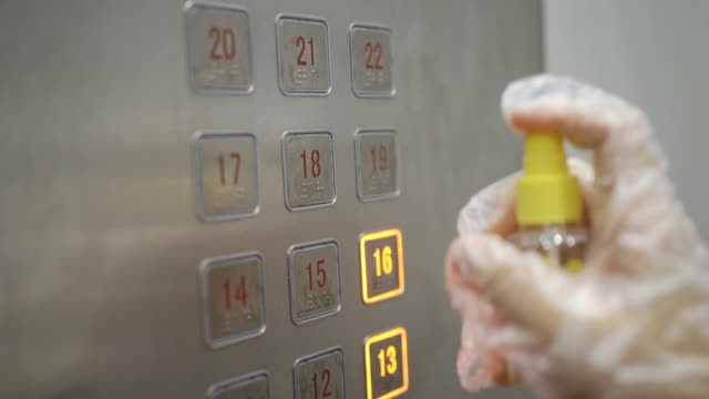 people wearing glove using spray alcohol for elevator button in apartment cleaning covid-19 virus in routine - hand on glass covid video stock e b–roll