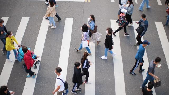 People wearing masks walking on zebra crossing