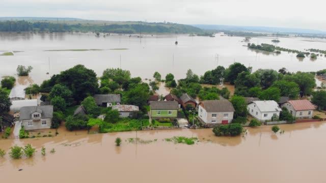 persone che si trovano in una casa allagata da un fiume che ha traboccato dopo le inondazioni della pioggia. catastrofe ecologica e villaggio e case allagati - fenomeno naturale video stock e b–roll