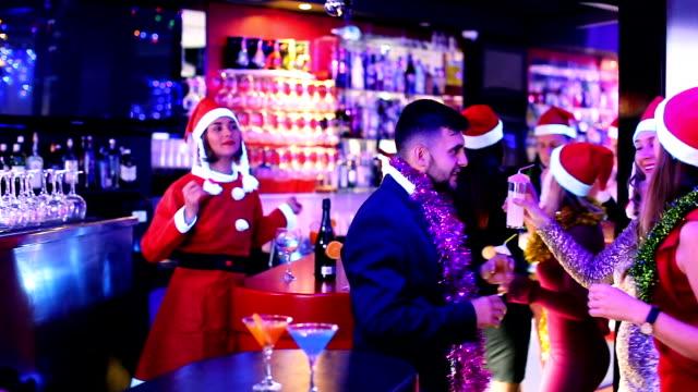 vídeos de stock, filmes e b-roll de pessoas com cocktails de chapéu de papai noel na boate - festa da empresa