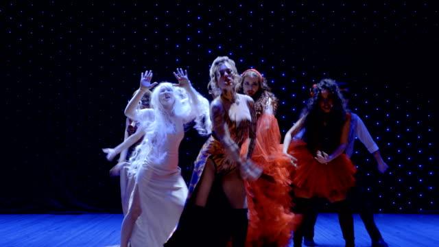 stockvideo's en b-roll-footage met mensen met ongewone verschijning dansen in het licht van schijnwerpers in theater - vetschmink