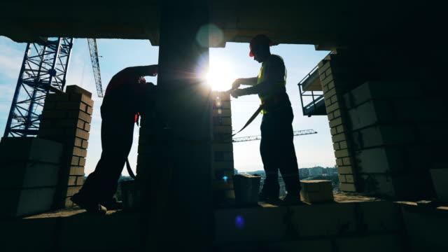 la gente lavora in un cantiere, posando mattoni. - operatore edile video stock e b–roll
