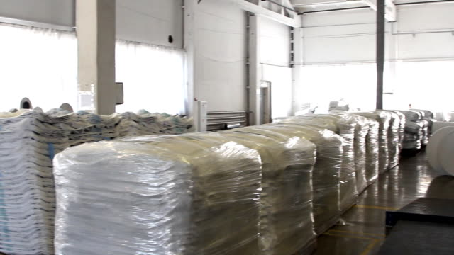 People work in large warehouse with goods at factory