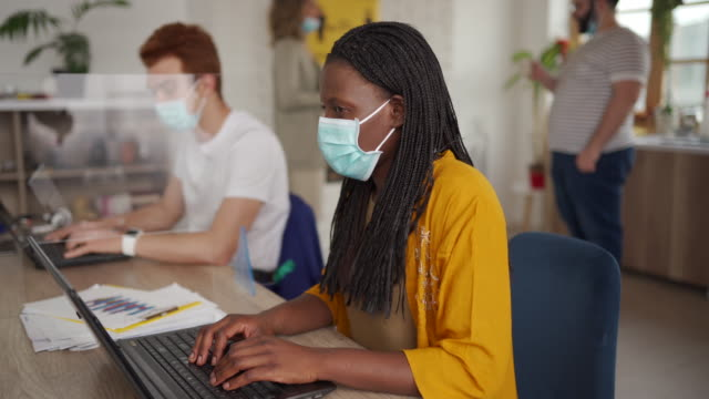 People working with protective masks in office video