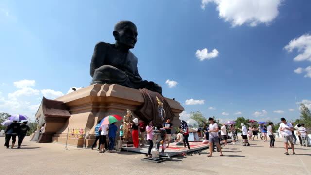 People worship around a Buddha statue video