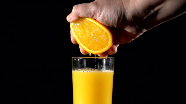 People's hand squeeze the orange fresh juice in glass, slow moti video
