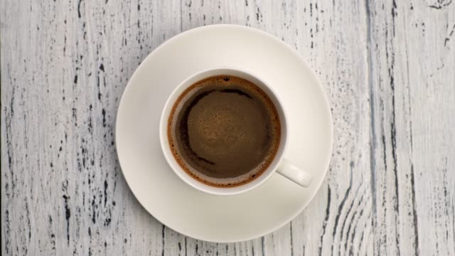 Perfect breakfast. Black frothy coffee in white cup over wooden grunge background. Top down view