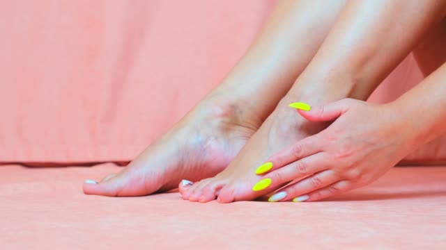 perfect clean female feet . beautiful and elegant groomed girl's hand touching her foot . spa ,scrub and foot care - pedicure filmów i materiałów b-roll