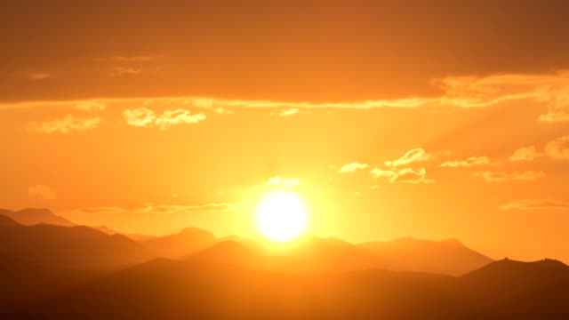 Perfect sunrise with mountains with big orange sun and decent lens flair