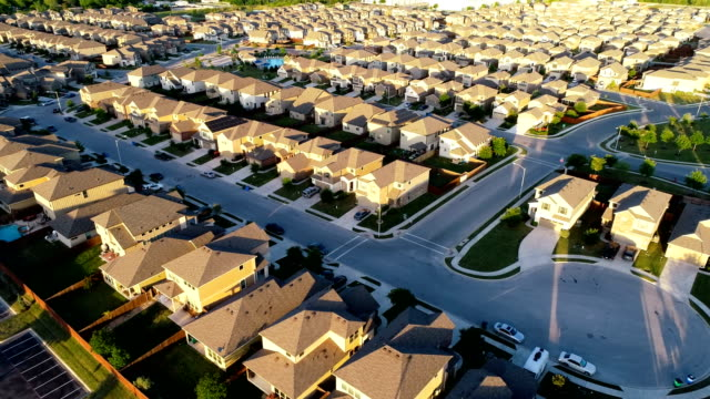 perfect sunset golden hour home ownership suburb drone view endless houses in austin , texas - ripetizione video stock e b–roll
