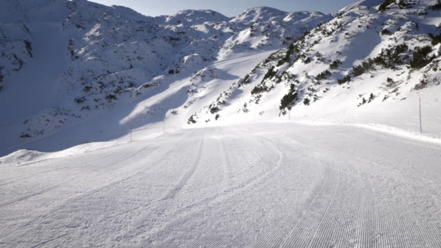 AERIAL Perfectly groomed ski trail in the morning sun video