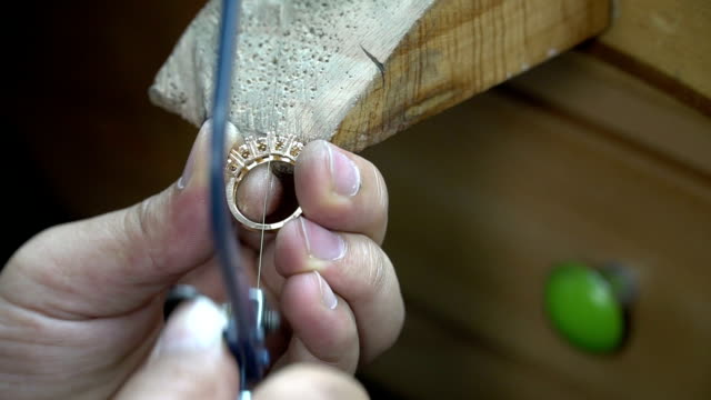 Perform a cut on a gold ring: goldsmith using a metal cutter video