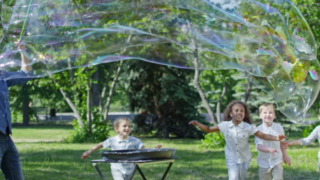 Performer Launching Huge Soap Bubble for Little Girl and Boys SLOWMO Three blonde boys and little African girl running and bursting huge soap bubble blown with tri-strings wand by professional performer in the park giant fictional character stock videos & royalty-free footage