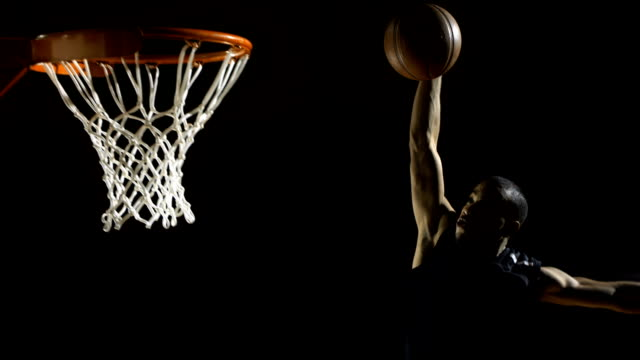 Performing A Slam Dunk (Super Slow Motion) HD1080p: SUPER SLOW MOTION shot of a professional basketball player jumps and performing a slam dunk with one hand. basketball stock videos & royalty-free footage