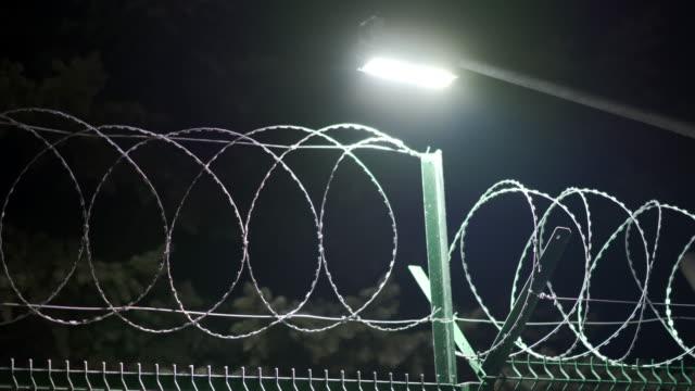 vídeos y material grabado en eventos de stock de sistema de vallado de seguridad perimetral, cerca de alambre de afeitar con iluminación por la noche - valla límite