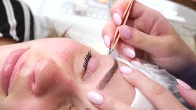 Permanent make-up for eyebrows of woman with thick brows in beauty salon. Closeup beautician doing coloring tattooing eyebrow Permanent make-up for eyebrows of woman with thick brows in beauty salon. Closeup beautician doing coloring tattooing eyebrow. molding a shape stock videos & royalty-free footage