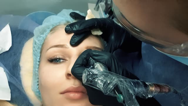 Permanent makeup. Permanent tattooing of eyebrows. Cosmetologist applying permanent make up on eyebrows- eyebrow tattoo. Permanent makeup. Permanent tattooing of eyebrows. Cosmetologist applying permanent make up on eyebrows- eyebrow tattoo. durability stock videos & royalty-free footage