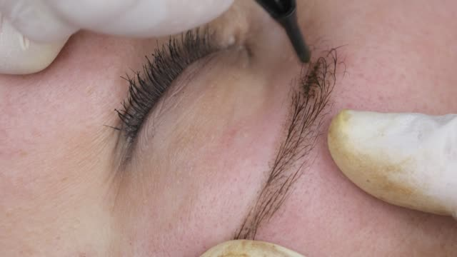 Permanent makeup, tattooing of eyebrows. Cosmetologist applying make up Permanent makeup, tattooing of eyebrows. Cosmetologist applying make up with machine for woman in beauty salon durability stock videos & royalty-free footage