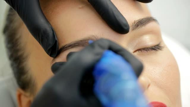 vídeos de stock e filmes b-roll de permanent tattooing of eyebrows - sobrancelha