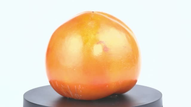 vídeos de stock e filmes b-roll de persimmon fruit spins on a white background. food. fruit. video. - diospiro