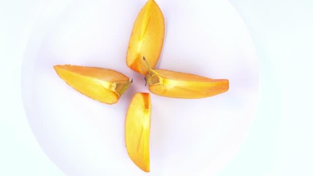 vídeos de stock e filmes b-roll de persimmon sliced on a white plate. the fruit. food. video. - diospiro