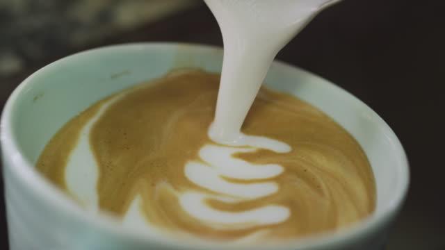 eine person gießt sorgfältig geschäumter milch in einen becher kaffee und macht latte art - barista stock-videos und b-roll-filmmaterial
