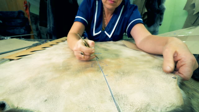 A person carves animal skin with a special knife, close up.