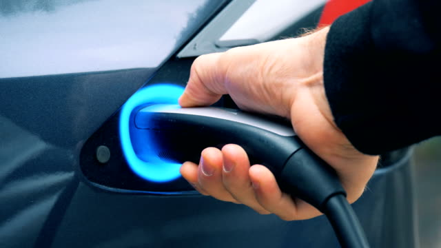 Person charging an electromobile, close up. video