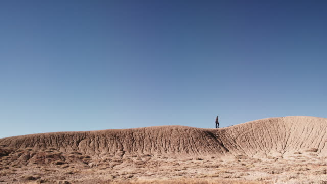 A Person Climbs Up and Walks Along a Striped and Eroded Desert Mountain Ridge Alone Against a Vibrant Blue Sky
