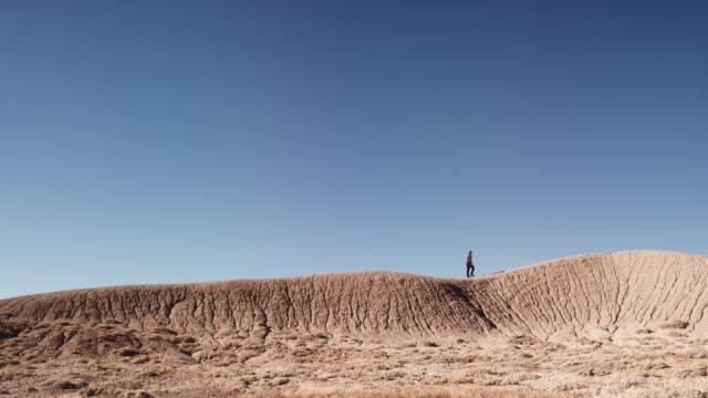 vídeos de stock, filmes e b-roll de uma pessoa sobe e caminha ao longo de uma crista listrado e erosão de deserto montanha sozinho contra um céu azul vibrante - erodido