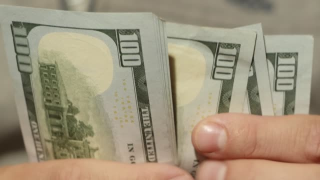 Person counts banknotes Man counts 100 dollar bills in his hands. A rich man and a thousand dollars. Hands are holding American money. Close-up of international banknotes us paper currency stock videos & royalty-free footage