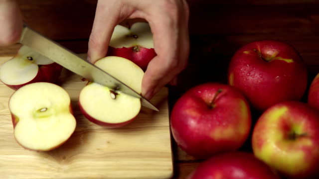 Person cuts an apple into slices on a cutting board.