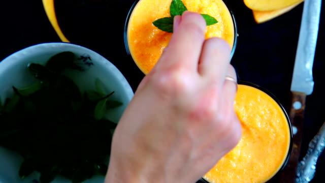 Person decorates orange smoothie video