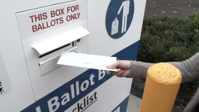 Person Delivers Ballot To Box On Election Day