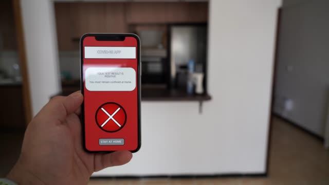"""eine person, die einen daumen nach unten hält ein smartphone, das eine coronavirus-app von der regierung entwickelt, die ihnen die covid 19 testergebnisse sagt und geben eine nachricht von """"zu hause bleiben"""", wenn es positiv ist - smartphone mit corona app stock-videos und b-roll-filmmaterial"""