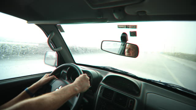 POV of person driving on a rainy road. Person traveling on road trip during rain in 4K video