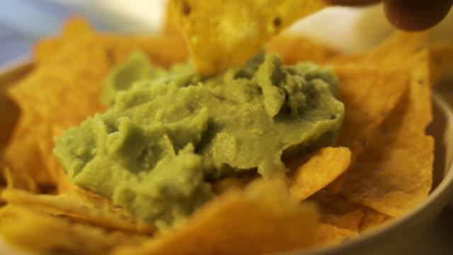 persona che mangia guacamole mentre raccoglie un chip - immergere video stock e b–roll