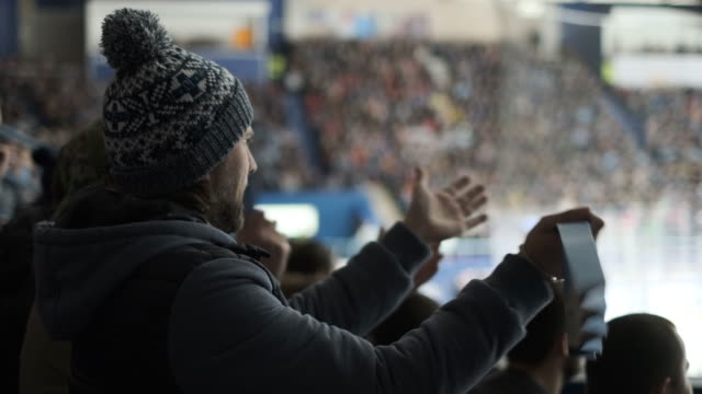 Person emotion cheering in crowd hockey close up fan watching sports match 4K.