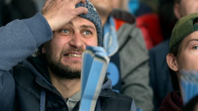 vídeos de stock e filmes b-roll de person expressive face grabs head lose team close up bad emotion fan of goal. - soccer supporter portrait