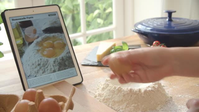 vidéos et rushes de personne après application d'une recette de pâtes à l'aide de tablette numérique - recette