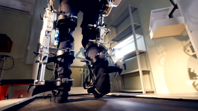 a person going through robot-assisted rehabilitation. - apparecchiatura medica video stock e b–roll