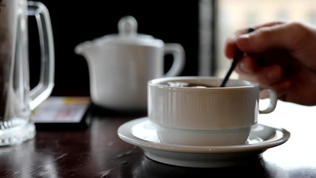 Person hand mixing sugar in a tea cup and drinking beverage video