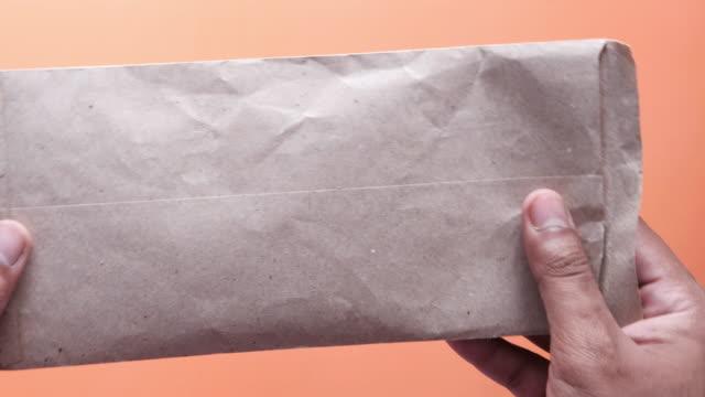 person hand sätta kontanter i ett kuvert - kuvert bildbanksvideor och videomaterial från bakom kulisserna
