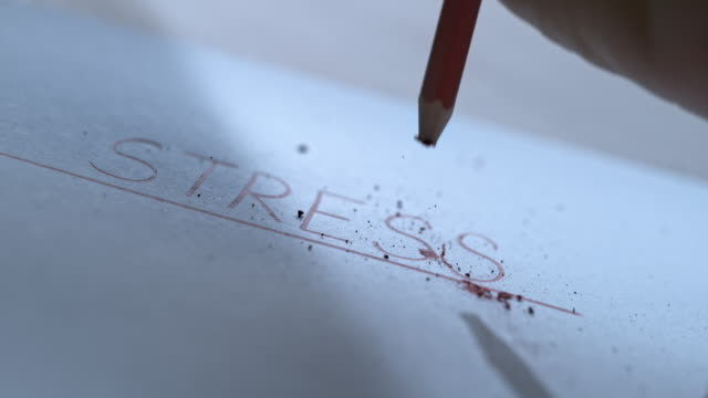 SLO MO LD Person hand repeatedly banging the tip of the colour pencil on the inscription